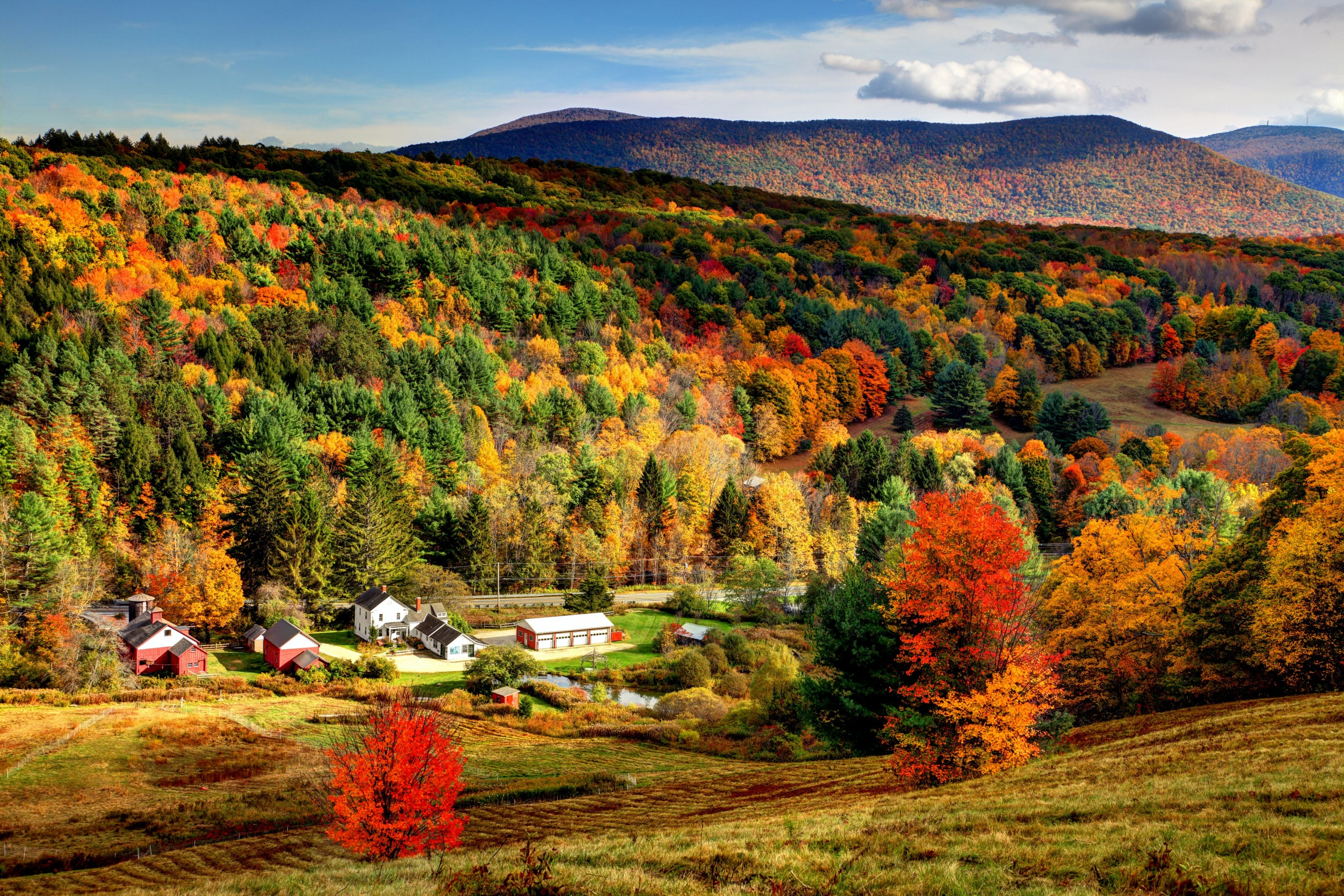 Fall colors fill a picturesque Massachusetts valley as a small village peeks through; New England fall foliage road trip