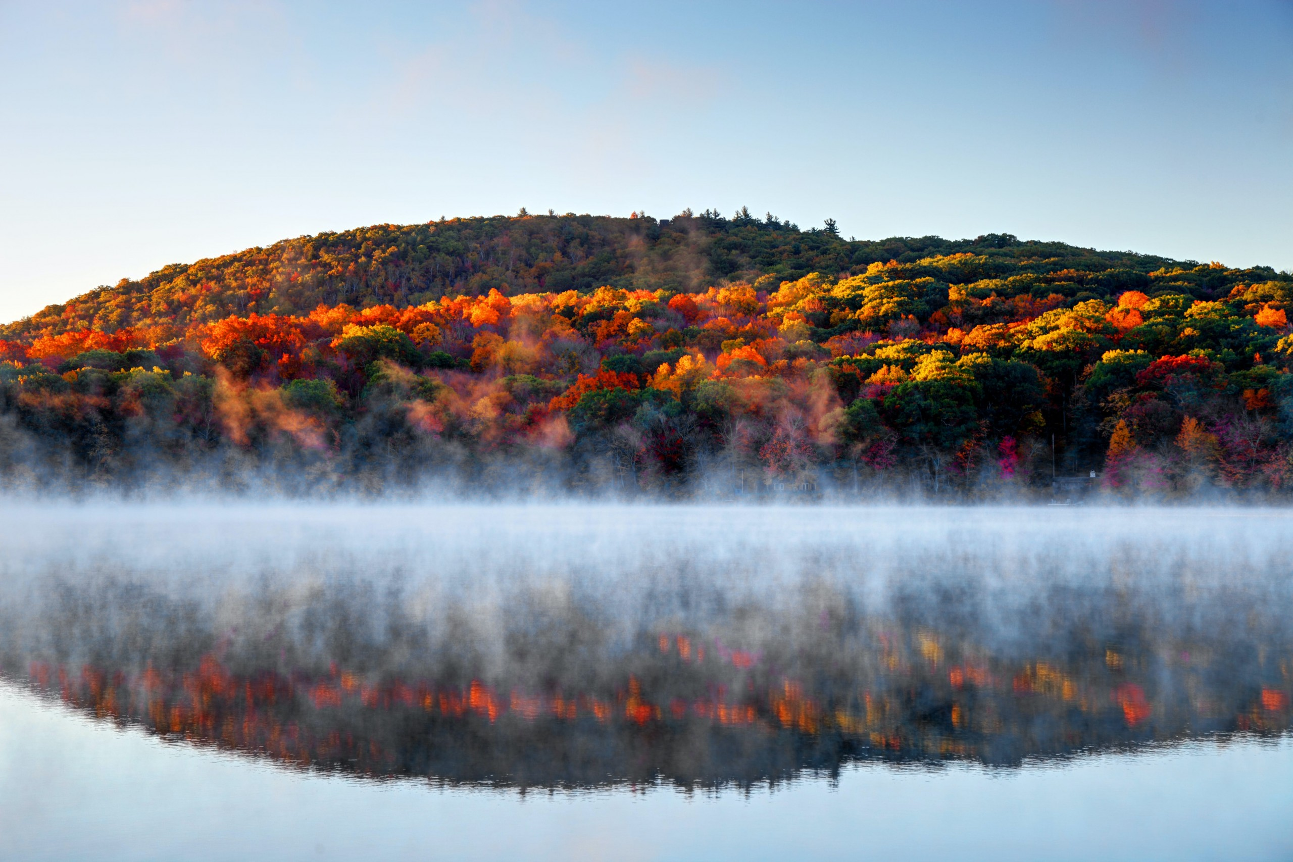 mist clings to the surface of a lake in Connecticut as red, orange, yellow and green leaves are reflected in its surface from a hill behind. New England fall foliage road trip