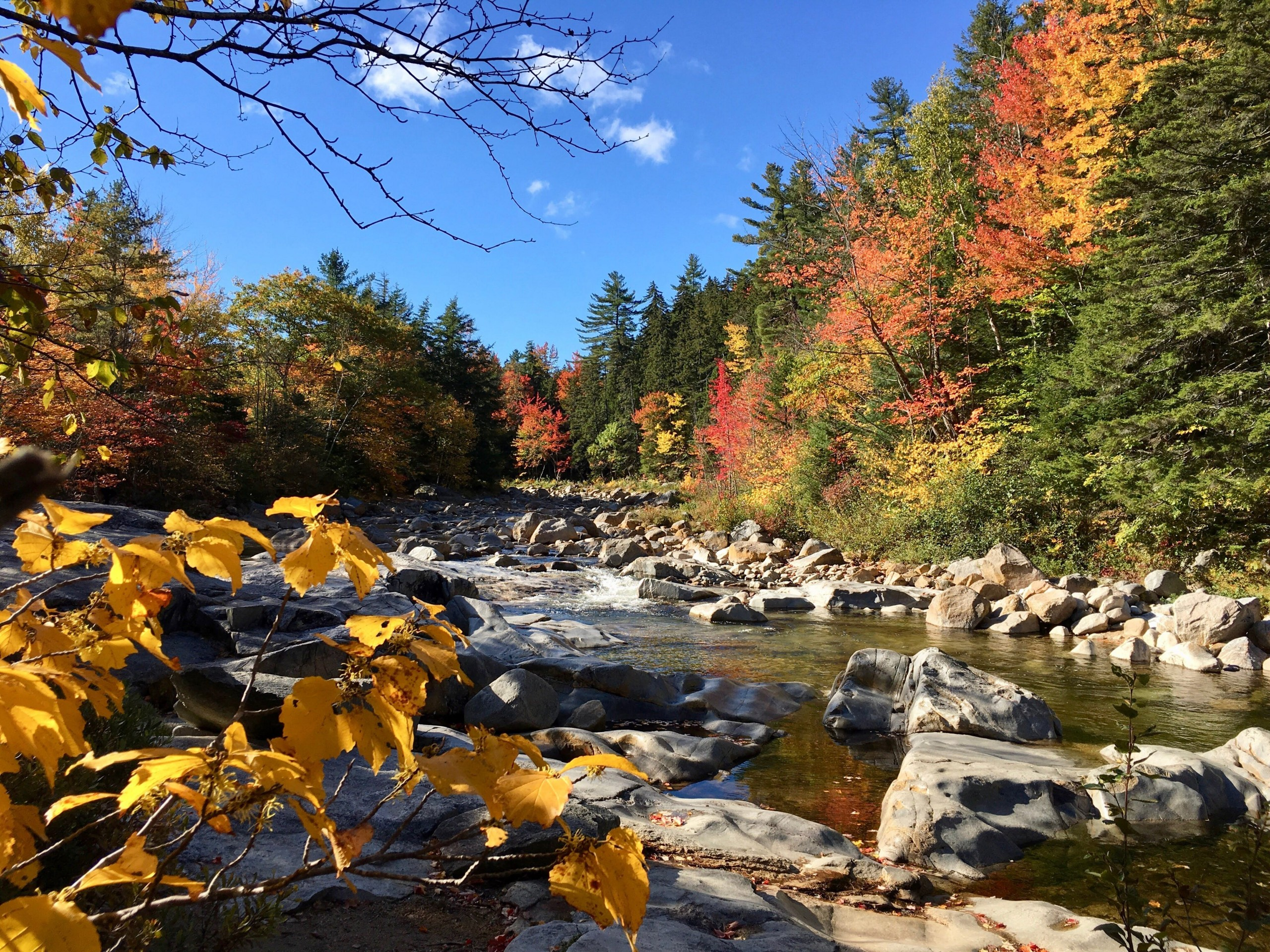 A stream tumbles over gray boulders as fall leaves stick out all around; New England fall foliage road trip