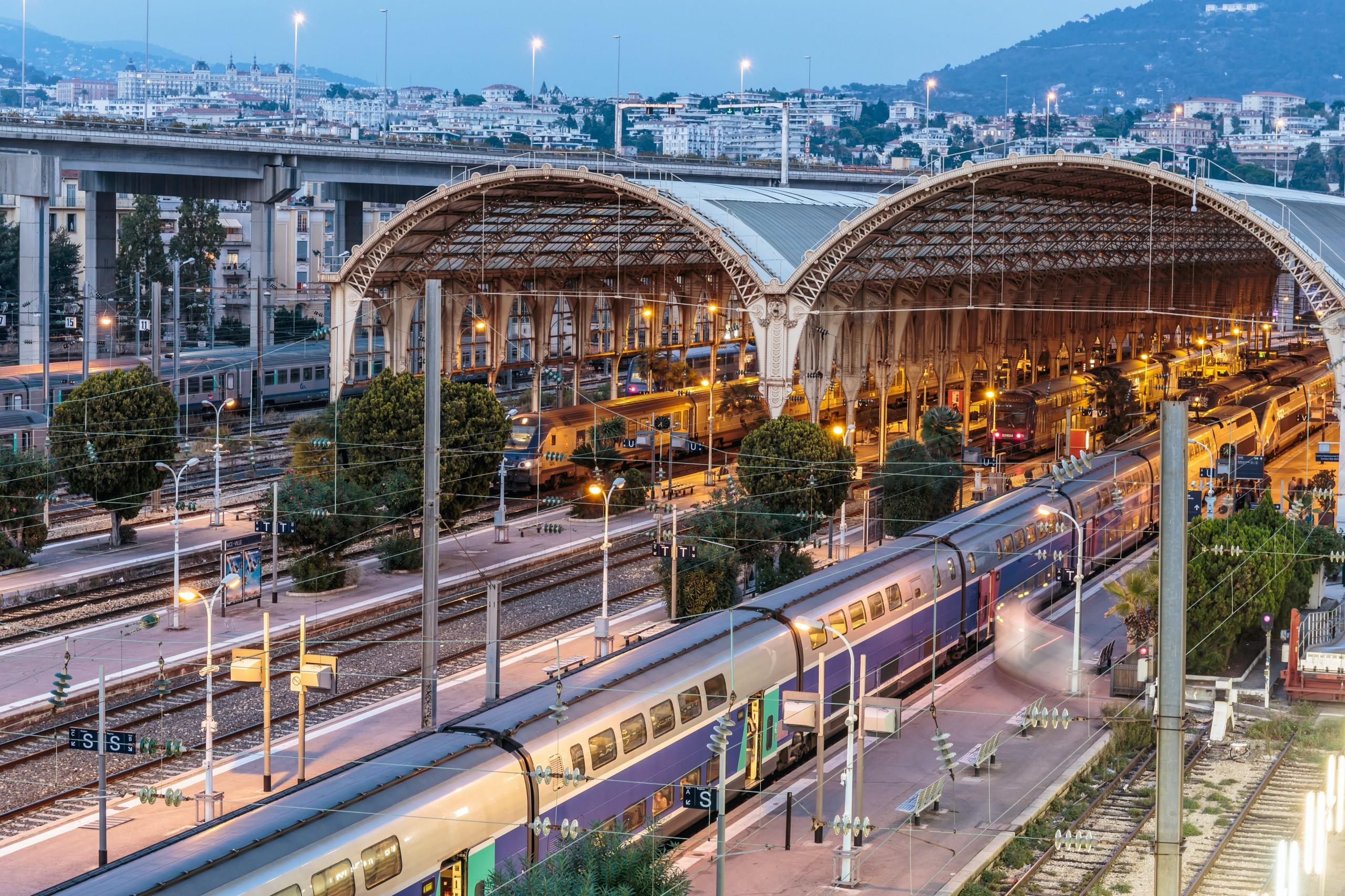 An aerial shot of a large station with two glass-and-steel arches forming the roof. Four trains wait at the platforms
